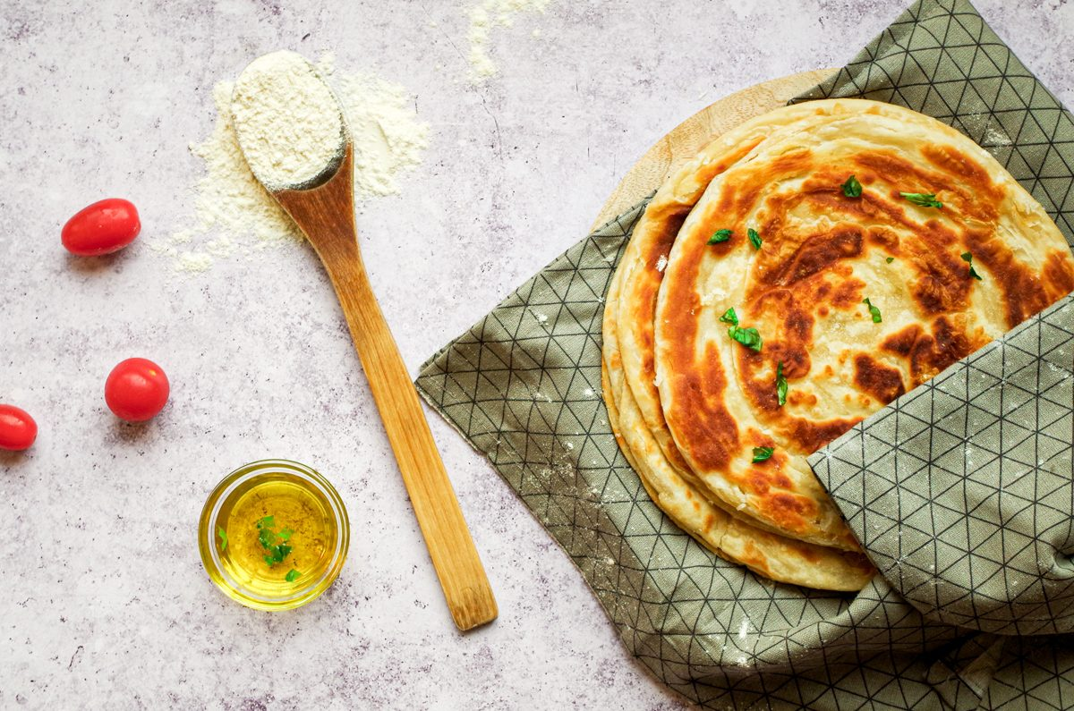 Four chapati breads on a kitchen towel.